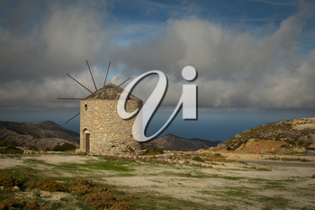 Beautiful view of a windmill on the top of a hill with a view on the ocean by a nice summer day in Naxos, Greece