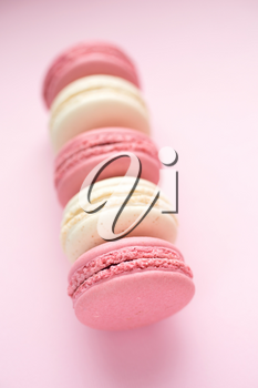 Row of traditional french macarons on pink background