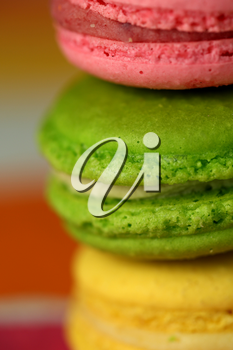 Pile of tasty macaroons on colourful background
