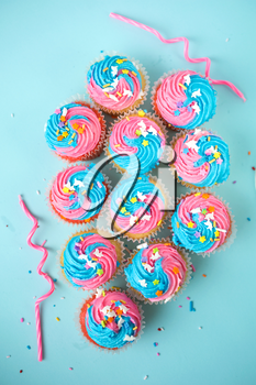 Top view of cupcakes with candles and  blue and pink icing on a blue background