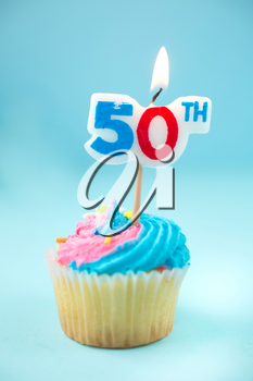 50th birthday cupcake with blue and pink icing on a blue background